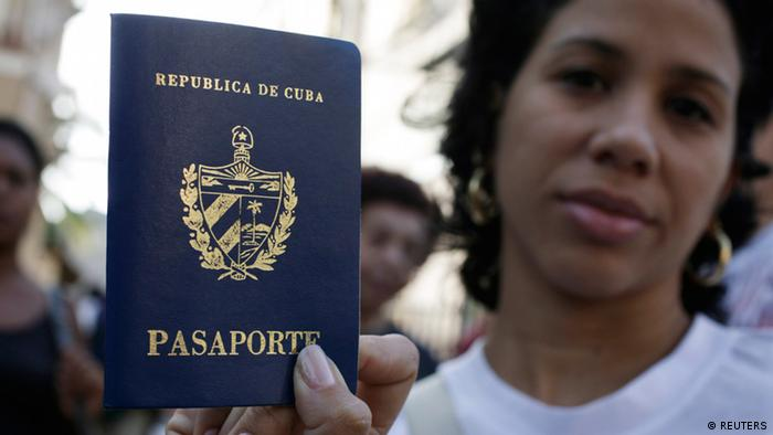 A woman shows her new passport while standing with others outside a passport office in Havana January 11, 2013. With paperwork in their hands and dreams of faraway places in their heads, Cubans waited in long lines this week to apply for passports ahead of a major liberalization of travel policies in place for more than half a century. Starting on January 14, most will be able to leave the country with just a passport and no need for much-hated exit visas and letters of invitation the communist government imposed in 1961 to slow a mass exodus of people fleeing after the 1959 revolution led by Fidel Castro. REUTERS/Enrique De La Osa (CUBA - Tags: SOCIETY IMMIGRATION POLITICS)