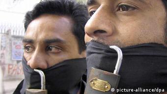 Zwei pakistanische Journalisten haben mit schwarzen Binden und einem Vorhängeschloss ihren Mund verschlossen