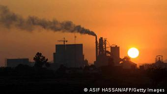 Smoke rises from a factory during the year's last sunset in Karachi on December 31, 2009