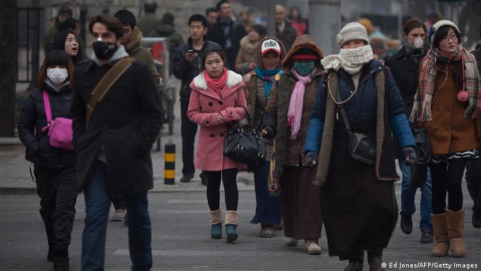 Pedestrians cross a street, some wearing face masks, during polluted weather in Beijing on January 13, 2013. Dense smog shrouded Beijing, with pollution at hazardous levels for a second day and residents advised to stay indoors, state media said. AFP PHOTO / Ed Jones (Photo credit should read Ed Jones/AFP/Getty Images)