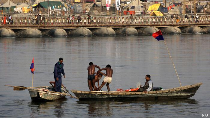 Water police guards rescue an Indian holy man stuck in the mid flow of the River Ganges at Sangam, the confluence of the rivers Ganges, Yamuna and mythical Saraswati, ahead of Maha Kumbh Mela, in Allahabad, India, Sunday Jan. 13, 2013 (AP Photo /Manish Swarup)