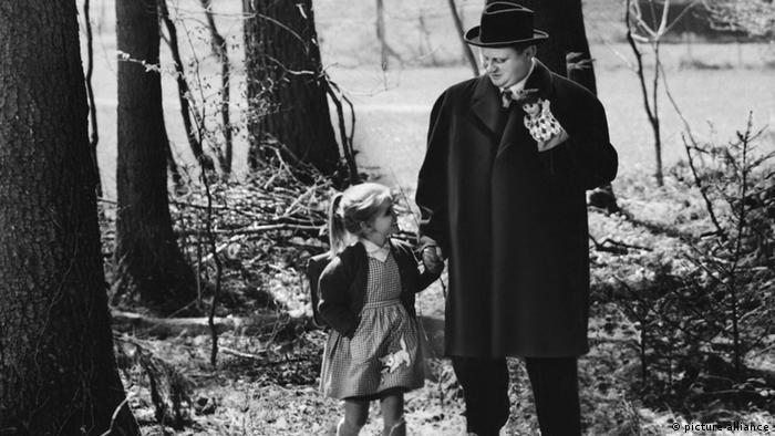 A man holds a puppet in one hand and the hand of a little girl in his other hand as they walk through the woods (picture-alliance)