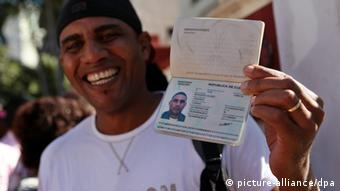 A man shows his passport as he leaves immigration offices in Havana, Cuba Alejandro Ernesto/EPA/dpa