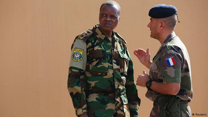 A French army officer (R) talks to his Malian counterpart outside where a meeting is taking place for the intervention force provided by the ECOWAS grouping of West African states, in Bamako January 15, 2013. France kept up its air strikes against Islamist rebels in Mali as plans to deploy African troops gathered pace on Tuesday amid concerns that delays could endanger a wider mission to dislodge al Qaeda and its allies. REUTERS/Joe Penney (MALI - Tags: CIVIL UNREST POLITICS CONFLICT)