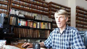 Joachim Oelsner im Arbeitszimmer, in Hintergrund eine riesige Sammlung mit Musikcassetten (Foto: Aya Bach)