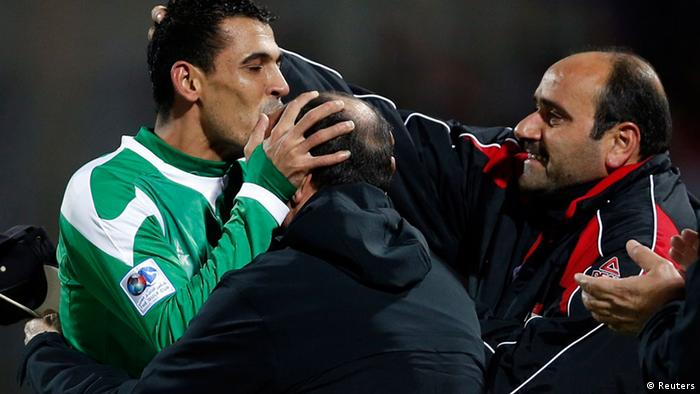 Iraq's Younis Mahmoud (L) kisses his coach Hakim Shaker (C) after scoring against Bahrain during their Gulf Cup Tournament semi-final soccer match in Isa Town, January 15, 2013. REUTERS/Fadi Al-Assaad (BAHRAIN - Tags: SPORT SOCCER)