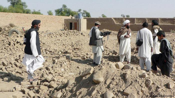 Local residents stand amid debris of a house destroyed in a US drone missile attack, in Bannu a town of restive North West Frontier Province (NWFP) near the Afghanistan border on 19 November 2008. At least four suspected Islamic militants were killed and seven more were injured on November 19, in a missile strike by a suspected pilotless US aircraft at a house in the village of Zandi Alikhel in the Jani Khel semi-tribal area of the Bannu district of NWFP, media reports said.