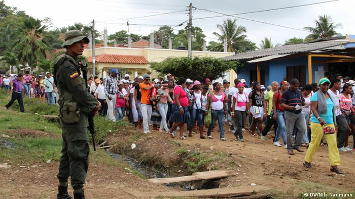 A soldier guarding a demonstration by displaced people in Colombia. (Photo: Nils Naumann / DW)