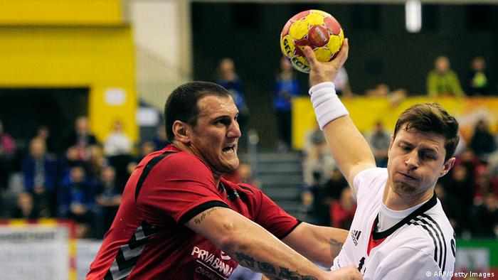 Montenegro's pivot Mladen Rakcevic (L) vies with Germany's centre back Martin Strobel (R) during the 23rd Men's Handball World Championships preliminary round Group A match Germany vs Montenegro at the Palacio de los Deportes de Granollers on January 16, 2013. (Photo: JOSEP LAGO/AFP/Getty Images)