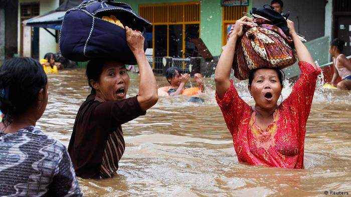 Women react as they flee from their flooded area in Jakarta (photo: REUTERS/Enny Nuraheni (INDONESIA)