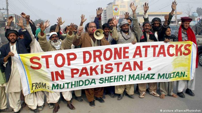 A large group of Pakistani protestors carries a sign that reads, Stop drone attacks in Pakistan.