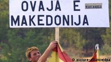 A boy attaches the Macedonian flag to a poster reading This is Macedonia on a road blockade between Skopje and Macedonian/Kosovo border Blace set up by Macedonian refugees from the town of Tetovo on Saturday 18 August 2001, to get NATO forces«attention. dpa