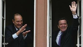 Gerhard Schröder und Jacques Chirac winken aus einem Fenster in Blomberg
