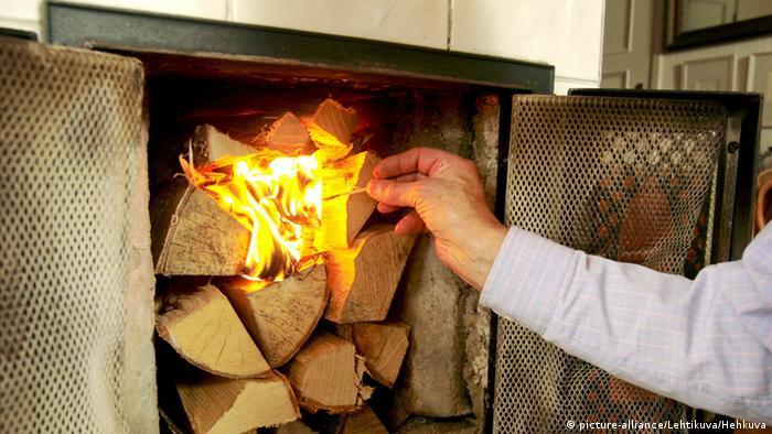 Man lighting a fire in a fireplace.