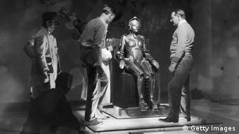 Fritz Lang und seine Metropolis-Filmcrew stehen vor einem sitzenden Roboter.