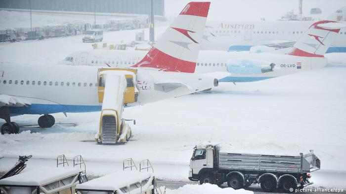 Since Donnerstag, 17. January, snow has hampered aviation in Vienna's Schwechat airport. An truck carries away snow. In the background: aircraft.