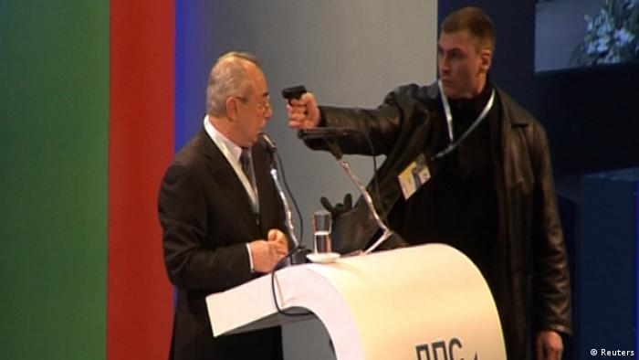 An unidentified man (R) attacks Ahmed Dogan, leader of Bulgaria's Movement for Rights and Freedom (MRF) party, as he delivers his speech during his party's annual conference at the National Palace of Culture in Sofia in this still image taken from video footage on January 19, 2013. Dogan was attacked by a man carrying a gun during his speech at the party conference in Sofia on Saturday. The attacker was later arrested and Dogan escaped unhurt . REUTERS/Nikola Stoyanov/Bnews