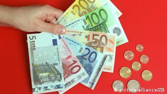 Bergen (Mecklenburg-Vorpommern): Das symbolische Foto zeigt eine Hand mit sechs der sieben neuen Euro-Banknoten und die acht Euro-Münzen in den Nennwerten 1 Cent bis 2 Euro, aufgenommen am 28.11.2001 in einer Sparkasse in Bergen. Nicht mit abgebildet ist die 500-Euro-Banknote. Die ab dem 01.01.2002 gültigen Banknoten sind in den Hauptfarben Grau (5er), Rot (10er), Blau (20er), Orange (50er), Grün (100er), Gelb-Braun (200er) und Lila (500er) gehalten. Ab dem 01.01.2002 ist der Euro das offizielle Zahlungsmittel in den Ländern Belgien, Deutschland, Finnland, Frankreich, Griechenland, Irland, Italien, Luxemburg, Niederlanden, Österreich, Portugal und Spanien. (STR415-031201)