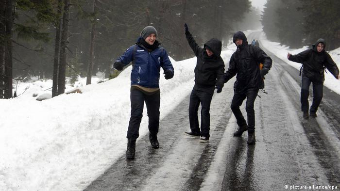 Eine Gruppe Jugendlicher schlittert auf der für den öffentlichen Fahrzeugverkehr gesperrte Brockenstraße im Harz (Foto: dpa)