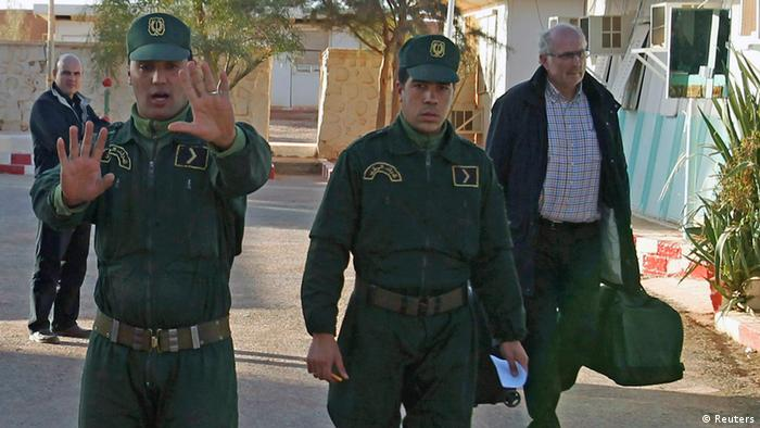 REFILE - ADDING NAME OF NORWEGIAN HOSTAFE Algerian Gendarme escort a freed Norwegian hostage Oddvar Birkedal (R) at the police station in In Amenas January 19 , 2013. The Algerian army on Saturday carried out a final assault on al Qaeda-linked gunmen holed up in a desert gas plant, killing 11 of the Islamists after they took the lives of seven more foreign hostages, a local source and the state news agency said. REUTERS/Louafi Larbi (ALGERIA - Tags: CIVIL UNREST POLITICS ENERGY)