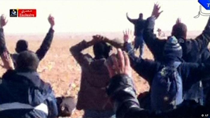 In this image made from video, a group of people believed to be hostages kneel in the sand with their hands in the air at an unknown location in Algeria. An Algerian security official says de-mining squads searching for explosives found numerous bodies Sunday, Jan. 20, 2012 at a gas refinery where Islamic militants took dozens of foreign workers hostage. (Foto:Ennahar TV/AP/dapd) ALGERIA OUT, TV OUT