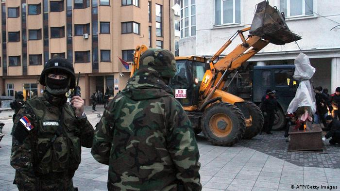 GettyImages 159757928 Serbian gendarmes secure the area as a bulldozer lifts up to remove the monument of the Liberation Army of Presevo, Medvedja and Bujanovac (UCPMB) in the town of Presevo on January 20, 2013. Serbian police broke up Sunday morning a monument in memory of Albanian insurgents who fought Belgrade's forces during a conflict in 2001, a measure that could increase tensions in this part of the country. AFP PHOTO / SASA DJORDJEVIC (Photo credit should read SASA DJORDJEVIC/AFP/Getty Images)