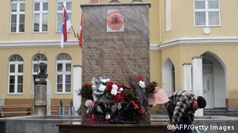 Ein alter Mann gießt Blumen vor dem Rebellen-Denkmal in Presevo (Foto: SASA DJORDJEVIC/AFP/Getty Images)