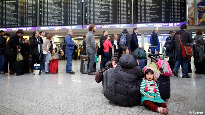 A girl sits on the floor in front of a queue at the departure area at the Fraport airport in Frankfurt January 21, 2013. Several flights were on delay and cancelled due to heavy weather conditions. REUTERS/Lisi Niesner (GERMANY - Tags: TRANSPORT)