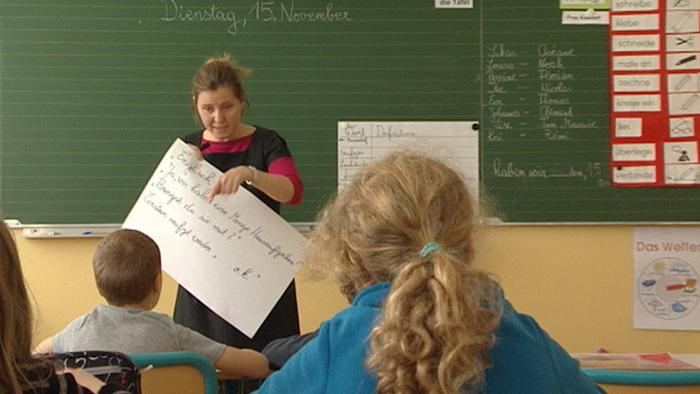 Teacher is holding up a paper at the blackboard, with students looking on. (Photo: Deutschland heute)