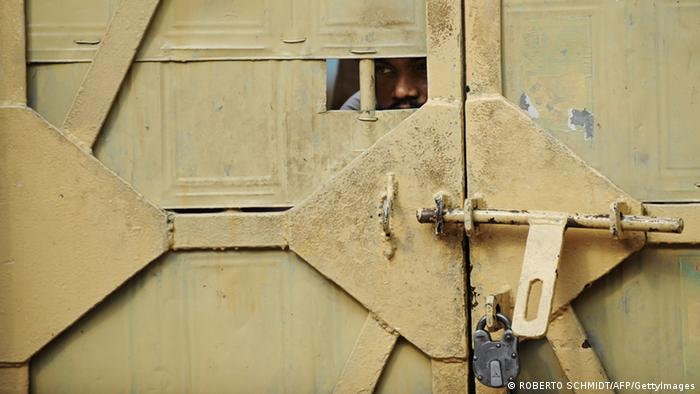 A man peeks through an opening of a door to a prison ward during a concert at the Tihar jail in New Delhi on April 26, 2012. The event was an unusual break from the daily routine at Tihar jail, a vast complex in the west of the Indian capital where 12,000 inmates ranging from trial suspects to convicted murderers are incarcerated. According to the International Center for Prison Studies, India houses some 330,000 inmates in its prisons, making it the fifth largest inmate population in the world. AFP PHOTO/ROBERTO SCHMIDT (Photo credit should read ROBERTO SCHMIDT/AFP/GettyImages)