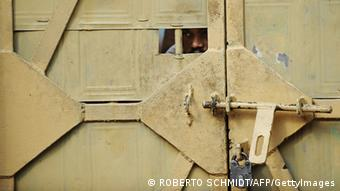 A man peeks through an opening of a door to a prison ward during a concert at the Tihar jail in New Delhi (Photo: ROBERTO SCHMIDT/AFP/GettyImages)