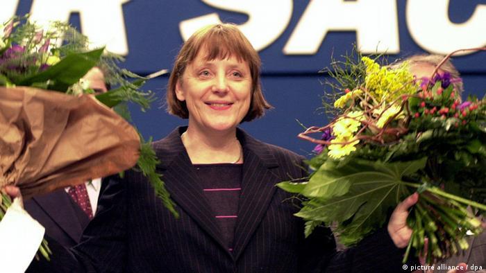 ARCHIV - Nach ihrer Wahl zur neuen Vorsitzenden der CDU bedankt sich Angela Merkel am 10.04.2000 in Essen bei den Delegierten des CDU-Bundesparteitages und winkt mit zwei Blumensträußen. Sie ist die erste Frau an der Spitze der Christdemokraten in Deutschland und leitet seit nunmehr zehn Jahren die Geschicke der Partei. Der Aufstieg der in der DDR aufgewachsenen Tochter eines evangelischen Pfarrers zeugt von Beharrlichkeit, Nervenstärke und Härte. Foto: Michael Jung (zu dpa-Themenpaket vom 05.04.2010 - Wiederholung vom 31.03.2010) +++(c) dpa - Bildfunk+++