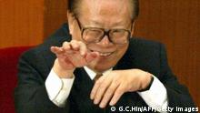 BEIJING, CHINA: Former Chinese president Jiang Zemin waves to a delegate during the closing session of the National People's Congress (NPC) in the Great Hall of the People in Beijing, 14 March 2004. China ended its annual session of parliament 14 March, with the rubber-stamp congress keeping its record of never opposing a government proposal or document intact for 50 straight years. AFP PHOTO/GOH CHAI HIN (Photo credit should read GOH CHAI HIN/AFP/Getty Images)