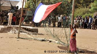 A boy stands next to a French national flag hung on a goalpost as French soldiers arrive in the Malian town of Diabaly, on January 21, 2013. Photo: ISSOUF SANOGO/AFP/Getty Images