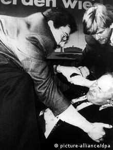 Helfer bemühen sich nach dem Anschlag auf den am Boden liegenden Oskar Lafontaine (Archivbild vom 25.04.1990). Der saarländische Ministerpräsident und SPD-Kanzlerkandidat war bei einer Wahlkampfveranstaltung am in der Stadthalle von Köln-Mühlheim von der 42-jährigen Arzthelferin Adelheid Streidel lebengefährlich verletzt worden. Hamburgs Justizsenator Roger Kusch (CDU) ist am Donnerstag (12.02.2004) bei einem Anschlag leicht verletzt worden. Nach Angaben der Polizei wurde der Senator in der Fußgängerzone von Hamburg-Neugraben am Vormittag von einer 41 Jahre alten Frau mit einem Klapp-Messer angegriffen. Kusch erlitt bei dem Anschlag eine blutende Stichwunde im Oberschenkel. Der Senator hatte im Bürgerschaftswahlkampf ohne Personenschutz an einem Informationsstand der CDU-Süderelbe gestanden und anschließend bei einem Gang über den Wochenmarkt den Kontakt zu den Anwohnern gesucht. dpa/lno (zu dpa 4228/lno 0320)