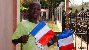 A young boy with flags in his hands. Photo: Katrin Gänsler
