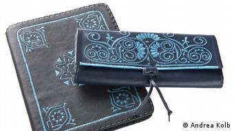 A black Abury tablet case and clutch bag. Aqua ribbon on black leather. Two Abury products, a black clutch bag and tablet case. (2011, Marrakesh, Morocco Name of the photographer/or scource: Andrea Kolb)