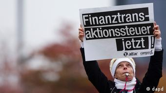 A woman holds a poster reading financial transaction tax now in front of German parliament buildings Photo:Markus Schreiber/AP/dapd