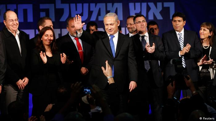 Israel's Prime Minister Benjamin Netanyahu (C) waves to supporters as he stands with his party members at the Likud party headquarters in Tel Aviv January 23, 2013. Hawkish Prime Minister Netanyahu emerged the bruised winner of Israel's election on Tuesday, claiming victory despite unexpected losses to resurgent centre-left challengers. REUTERS/Baz Ratner (ISRAEL - Tags: POLITICS ELECTIONS)