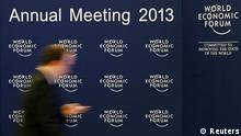 A man walks past the logo of the World Economic Forum (WEF) inside the Congress Hall at the Swiss Alpine resort of Davos January 22, 2013. The annual World Economic Forum held from January 23 to 27, 2013 in Davos. REUTERS/Pascal Lauener (SWITZERLAND - Tags: POLITICS BUSINESS)