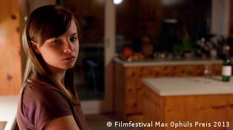 A girl looks plaintively to the side while standing inside a house (Filmfestival Max Ophüls Preis 2013)