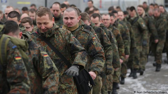 Men in green battle dress uniforms march in file Photo: Sean Gallup/Getty Images)