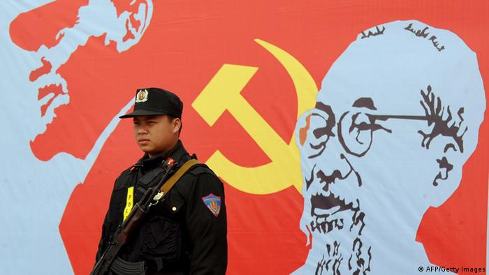 An armed policeman stands guard next to a portrait of late president Ho Chi Minh (R), founder of today's communist Vietnam,