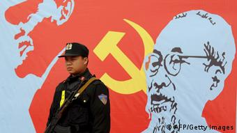 An armed policeman stands guard next to a portrait of late president Ho Chi Minh, founder of today's communist Vietnam, and Russian communist leader Vladimir Lenin (Photo: Hoang Dinh Nam)