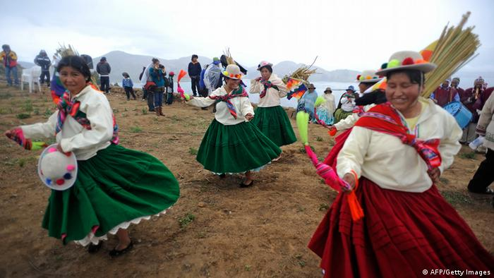 GettyImages 158438602 Aymara women dance during a ritual on Intja island, in Titicaca Lake, Bolivia on December 16, 2012, in the presence of Bolivian President Evo Morales and Minister of Foreign Affairs David Choquehuanca (out of frame). The rituals are part of preparations for summer solstice next December 21, and will include the sailing of a 15-meter bulrush boat called Tunupa. AFP PHOTO/Jorge Bernal (Photo credit should read JORGE BERNAL/AFP/Getty Images)