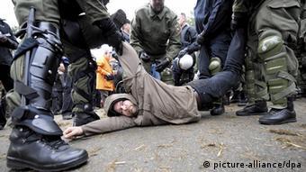 Polizisten halten einen Mann am Boden fest. Foto Peter Steffen dpa