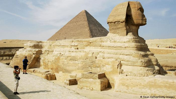 Tourists take pictures of the Sphinx as the Khufu pyramid looms behind it