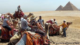 Туристы на верблюдах перед египетскими пирамидами