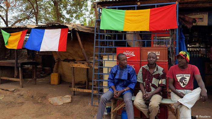 Men sit outside a shop as Malian and French flags decorate the area in Sevare, about 600 km (400 miles) northeast of the capital Bamako January 25, 2013. Government forces advanced into northern Mali on Friday and reached the town of Hombori, some 160 km (100 miles) south of the Islamist rebel stronghold of Gao, after French air strikes drove back the militants, military sources said. REUTERS/Adama Diarra (MALI - Tags: POLITICS CONFLICT SOCIETY)