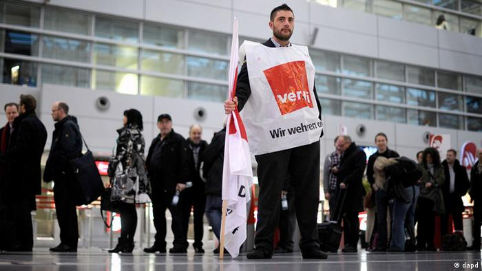 A striking worker in front of a queue at Düsseldorf airport (zu dapd-Text)